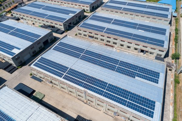 aerial view of solar panels on the roofs of industrial plants